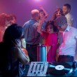 Young couple dancing at party with female dj — Stock Photo