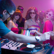 Male dj playing music with turntables and headphones at a party with dacing in front of him wearing sunglasses, with other in background and colorful lights — Stock Photo
