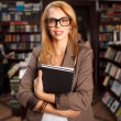 Cool geeky girl in bookshop — Stock Photo