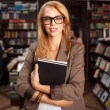 Cool geeky girl in bookshop — Stock fotografie