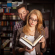Young couple reading a book in a library — Stock Photo