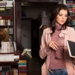 Young caucasian brunette girl in a bookstore — Foto de Stock