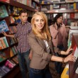 Beautiful young woman in bookshop — Stock Photo