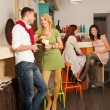 Young man courting a blonde girl in colorful cafe — Stock Photo #19986959