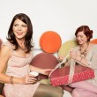 Stock Photo: Happy girls unwrapping present