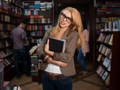 Young attractive blonde girl in bookstore — Stock Photo