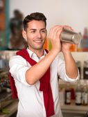 Attractive bartender mixing a drink — Stock Photo