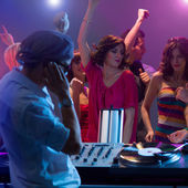 Male dj mixing music at party with dancing — Stock Photo