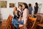 Happy friends at a photography exhibition — Stock Photo