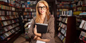 Cool geeky girl in bookshop — Stock Photo