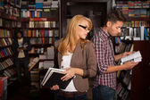 Young girl spying on a boy in a bookshop — Stock Photo