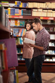 Young guy reading in bookstore — Stock Photo