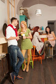 Young man courting a blonde girl in colorful cafe — Stock Photo
