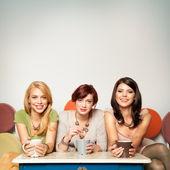 Happy girlfriends with coffee mugs — Stock Photo