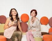 Chicas atractivas en el sofá con tazas de café riendo — Foto de Stock