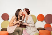 Girls whispering a secret and laughing — Stock Photo