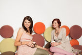 Beautiful caucasian girls on colorful sofa — Stock Photo