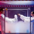 Постер, плакат: Two scientists experimenting with steamy reactions