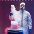 Chemist experimenting with vapors on blue barrel — Stock Photo
