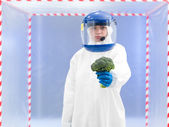 Person in protective suit presenting a vegetable — Stock Photo