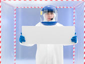 Person in protective suit holding white board — Stock Photo