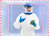 Person in protective suit injecting a vegetable — Stock Photo