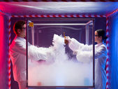 Two scientists conducting tests in sterile chamber — Stock Photo