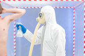 Biohazard geared person disinfecting a man — Stock Photo