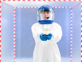 Person in protective suit holding a plant — Stock Photo