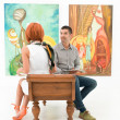 People looking at colorful paintings in art gallery — Foto de Stock