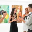 Female artist talking about her works — Stock Photo