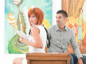 Beautiful redhead woman in an art gallery — Stock Photo