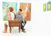 Young couple contemplating artworks — Foto Stock