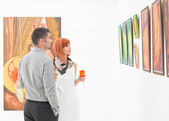 People looking at art gallery paintings — Stock Photo