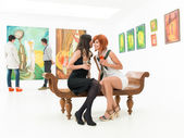 Sharing secrets at art exhibition — Stock Photo