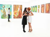 Women gossiping in art gallery — Stock Photo