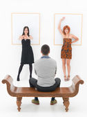 Man entertained by two women in an art gallery — Stock Photo