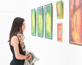Woman admiring colorful painting — Stock Photo