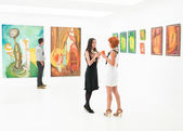 Beautiful women at exhibition opening — Stock Photo