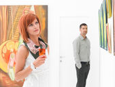 Man admiring a beautiful woman at painting exhibition — Stock Photo