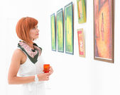 Woman admiring paintings in an art gallery — Stock Photo