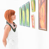 Woman admiring a painting in a museum — Stock Photo