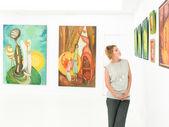 Vista lateral de uma jovem mulher bonita em pé em uma galeria de arte, contemplando quadros exibidos na frente dela — Foto Stock