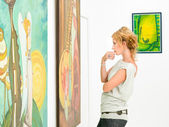 Woman contemplaing colorful paintings — Stock Photo