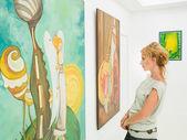 アート ギャラリーで絵画を見つめる女性 — ストック写真