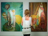 Woman contemplating colorful paintings — Stockfoto