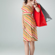 Young woman in colourful outfit holding some shopping bags, smil — Stock Photo #5254834