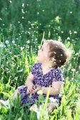 Meisje in een paardebloem veld — Stockfoto