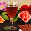 Glass of wine, chocolate and flowers. — Stock Photo