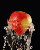 Apple in a jet of water. — Stock Photo